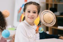 Маленькая школьница усмехаясь на камере пока сидящ в классе Стоковое Фото