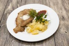Маленькая шницель сосиски с кипеть картошками и кетчуп Послуженный на белой плите фарфора на деревянной предпосылке Стоковые Фото
