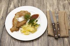 Маленькая шницель сосиски с кипеть картошками и кетчуп Послуженный на белой плите фарфора с вилкой и ноже на деревянном backgr Стоковая Фотография