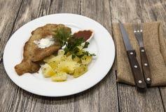 Маленькая шницель сосиски с кипеть картошками и кетчуп Послуженный на белой плите фарфора с вилкой и ноже на деревянном backgr Стоковое фото RF