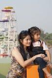 Маленькие азиатские девушка и мама в парке атракционов. Стоковые Фото