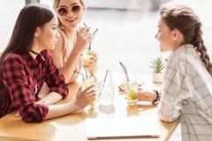 Маленькие девочки выпивая коктеили совместно пока сидящ на таблице в кафе Стоковые Изображения