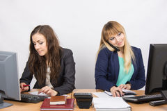 Маленькие девочки в офисе, одном работают в компьютере, другом на телефоне и смотреть экран Стоковое Изображение RF