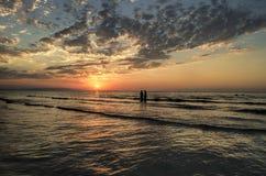 Маленькие девочки в теплой воде на заходе солнца Шикарные цвета в небе и море Люди стоя и наблюдая к заходу солнца на Каспийском  Стоковая Фотография