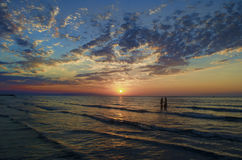 Маленькие девочки в теплой воде на заходе солнца Шикарные цвета в небе и море Люди стоя и наблюдая к заходу солнца на Каспийском  Стоковые Изображения RF