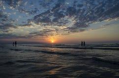 Маленькие девочки в теплой воде на заходе солнца Шикарные цвета в небе и море Люди стоя и наблюдая к заходу солнца на Каспийском  Стоковое Фото