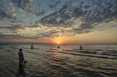 Маленькие девочки в теплой воде на заходе солнца Шикарные цвета в небе и море Люди стоя и наблюдая к заходу солнца на Каспийском  Стоковая Фотография RF