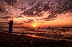 Маленькие девочки в теплой воде на заходе солнца Шикарные цвета в небе и море Люди стоя и наблюдая к заходу солнца на Каспийском  Стоковое Изображение