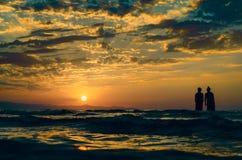 Маленькие девочки в теплой воде на заходе солнца Шикарные цвета в небе и море Люди стоя и наблюдая к заходу солнца на Каспийском  Стоковые Фотографии RF