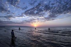 Маленькие девочки в теплой воде на заходе солнца Шикарные цвета в небе и море Люди стоя и наблюдая к заходу солнца на Каспийском  Стоковое фото RF