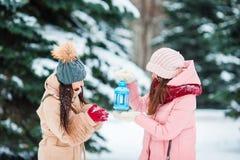 Маленькие девочки держа свет горящей свечи рождества outdoors на красивый день снега зимы и греют их руки Стоковая Фотография RF