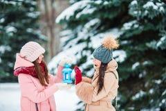Маленькие девочки держа свет горящей свечи рождества outdoors на красивый день снега зимы и греют их руки Стоковое Фото