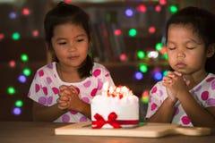Маленькие девочки делают сложенную руку для того чтобы пожелать хорошие вещи для их дня рождения Стоковое Фото