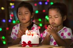 Маленькие девочки делают сложенную руку для того чтобы пожелать хорошие вещи для их дня рождения Стоковое Изображение