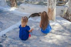 Маленькие девочки играют с котом на улицах  стоковые изображения rf