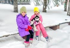 Маленькие девочки играя с осиплой собакой на снеге Стоковое Изображение RF