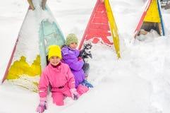 Маленькие девочки играя с осиплой собакой на снеге Стоковое фото RF