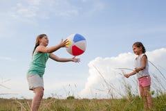 Маленькие девочки играя с шариком outdoors Стоковые Изображения RF