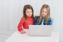Маленькие девочки используют компьтер-книжку на таблице на комнате Стоковое Изображение RF