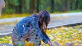 Маленькие девочки и счастливая мама наслаждаются днем падения в парке осени outdoors Семейный отдых осени сток-видео