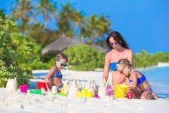Маленькие девочки и счастливая мать играя с пляжем Стоковые Изображения