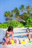Маленькие девочки и счастливая мать играя с пляжем Стоковое фото RF
