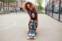 Маленькие девочки катаясь на коньках в баскетбольной площадке Стоковое Изображение RF