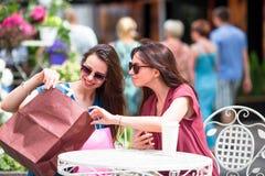 Маленькие девочки моды с хозяйственными сумками в внешнем кафе Продажа, защита интересов потребителя и концепция людей Стоковые Фото