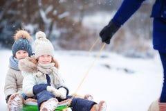 Маленькие девочки наслаждаются ездой саней Sledding ребенка Стоковые Изображения RF