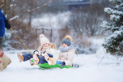 Маленькие девочки наслаждаются ездой саней Sledding ребенка Стоковые Фото