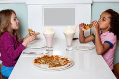 Маленькие девочки наслаждаясь пиццей в ресторане Стоковое Фото