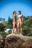 Маленькие девочки на камнях на пляже Стоковая Фотография