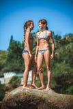 Маленькие девочки на камнях на пляже Стоковое Изображение