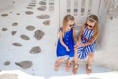Маленькие девочки на улице типичной греческой традиционной деревни в Греции Стоковое Изображение RF