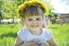 Маленькие девочки сидя в поле в венке одуванчиков. Стоковые Изображения RF
