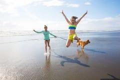 Маленькие девочки скача на пляж стоковое фото rf