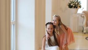 Маленькие девочки смотрят вне окно, объятие и смех видеоматериал