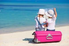 Маленькие девочки с большими чемоданом и картой на тропическом Стоковое фото RF