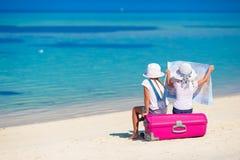 Маленькие девочки с большими чемоданом и картой на тропическом Стоковые Фото