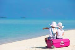 Маленькие девочки с большими чемоданом и картой на тропическом Стоковые Фотографии RF