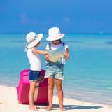 Маленькие девочки с большими чемоданом и картой на тропическом Стоковое Фото