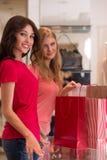 Маленькие девочки с хозяйственными сумками в магазине Стоковые Изображения