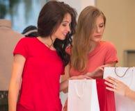 Маленькие девочки с хозяйственными сумками в магазине Стоковое фото RF