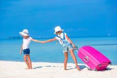 Маленькие девушки туристов с большим чемоданом на тропическом белом пляже перемещение карты dublin принципиальной схемы города ав Стоковое Изображение RF