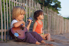 Маленькие дети имеют потеху на пляже захода солнца тропическом Стоковое Фото