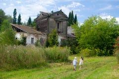 Маленькие дети идут к старому загубленному дому Стоковое Изображение
