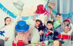 Маленькие дети обменивая подарки друг с другом во время партии Стоковые Изображения RF