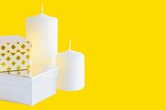 2 маленькие коробки и свечи подарка на желтой предпосылке Стоковое Изображение