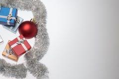 Маленькие коробки для подарка рождества, шариков рождества и сусали рождества на белизне Стоковое Фото