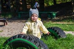 Маленькие красивые пальто, шляпа и джинсы младенца девушки играя в парке идя на зеленую траву делая их усмехаться и enjo первых ш Стоковые Изображения RF